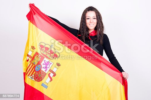537894724 istock photo Woman playing with a spanish flag, showing it. 537894724