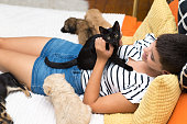 istock Woman playing with cat and dogs 1051356394