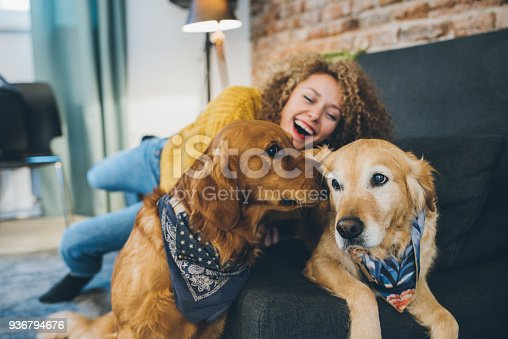 Woman playing with her dogs at home.