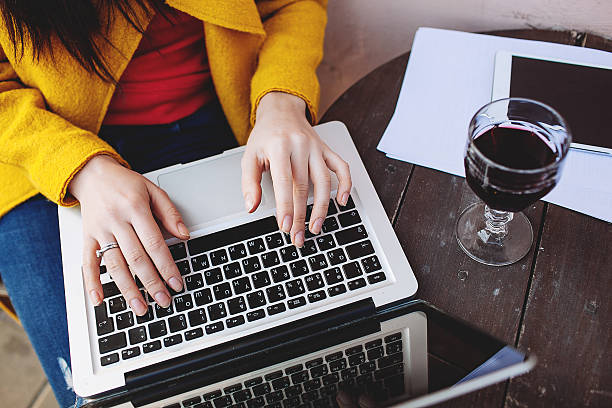 Woman playing with laptop in cafe with a glass of wine stock photo