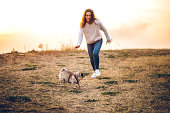 Young Caucasian beautiful woman playing with pug on meadow.