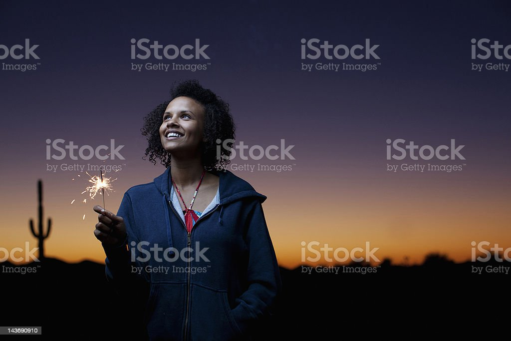 Woman playing with sparkler in desert stock photo