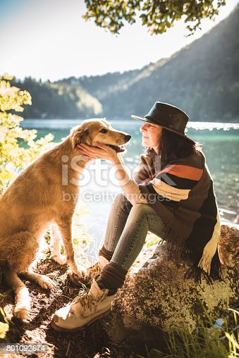 istock woman playing with the dog in the mountain 801092674