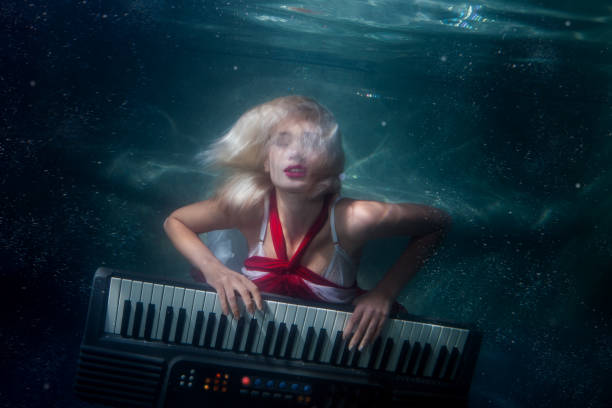 frau spielt musik, die unter wasser tauchen. - frau tiefer ausschnitt stock-fotos und bilder