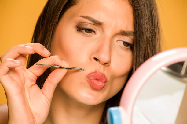 woman plucking her mustache with tweezers stock photo