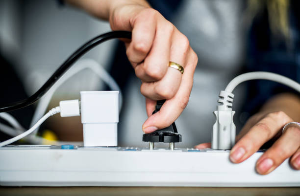 Woman plugging the wire to the outlet Woman plugging the wire to the outlet electrical outlet stock pictures, royalty-free photos & images
