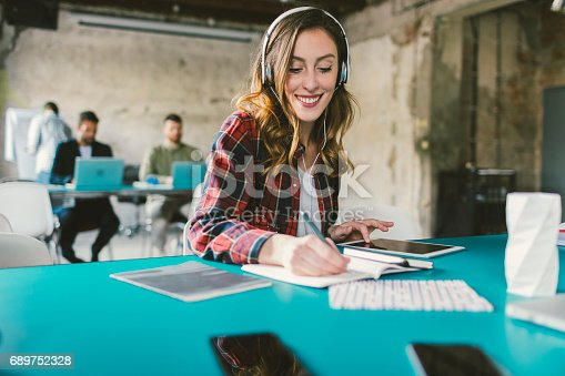 Young woman podcasting in modern office. Sitting with headphones, using digital tablet and writing