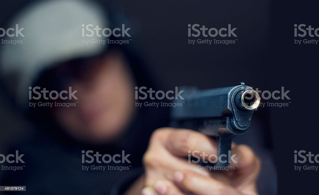 Woman pointing a gun at the target on dark background stock photo