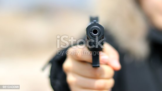 istock Woman pointing a gun at the target on soft background. 931040098