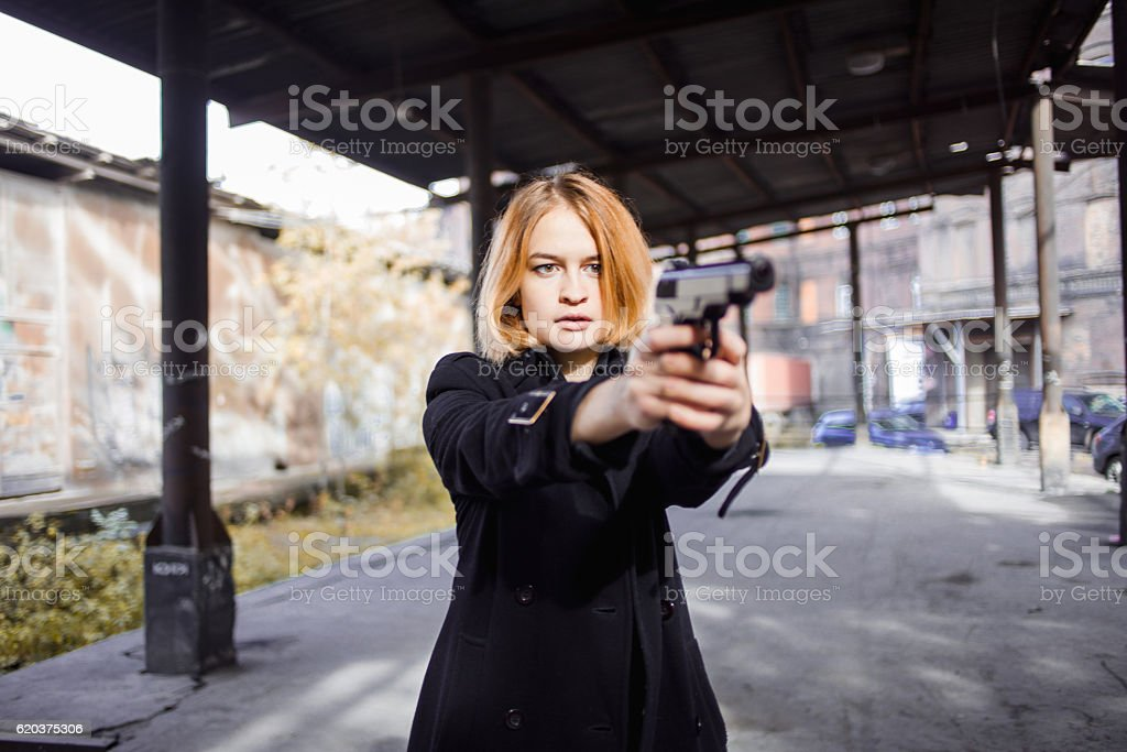 Woman pointing a gun. Mafia girl shooting at someone on foto de stock royalty-free