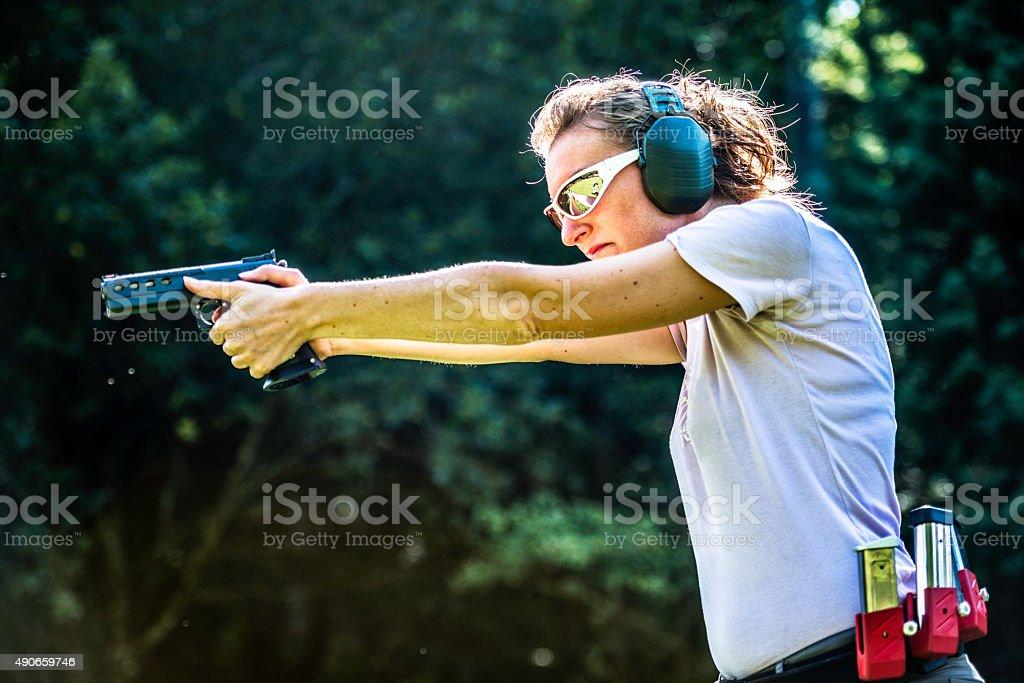 Mujer señalando una pistola - foto de stock