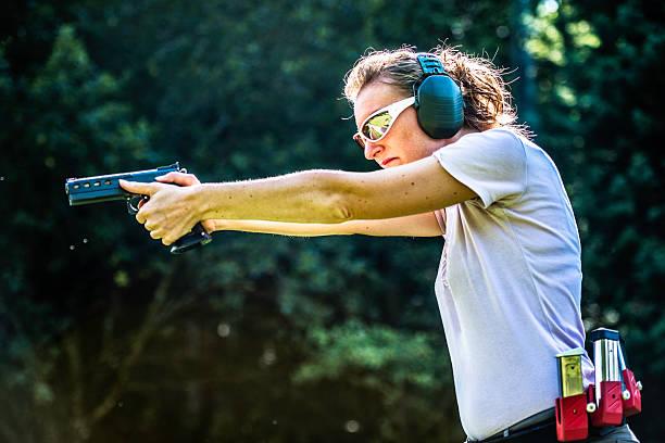 Femme pointant un pistolet - Photo