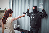 istock woman pointing a gun to a bandit who wear black mask and black clothes. bandit raised both hands to show his surrender. 1164148674