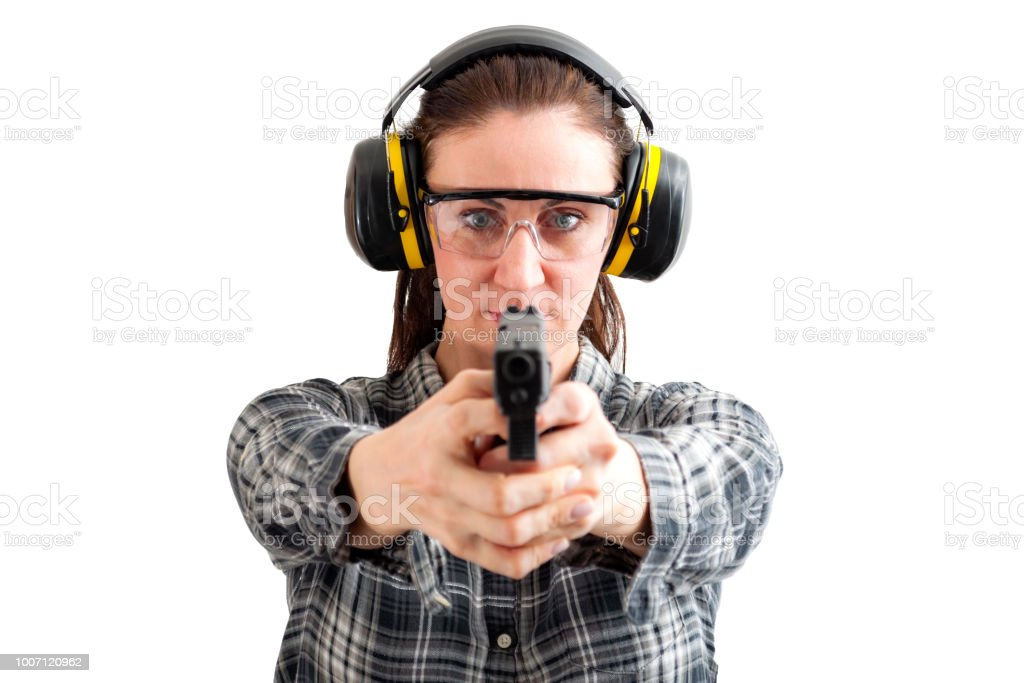 Woman pointing a handgun at the camera isolated on white stock photo