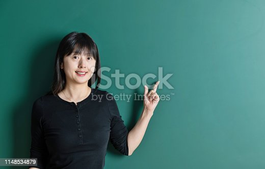 485083346 istock photo Woman pointing at a blackboard 1148534879