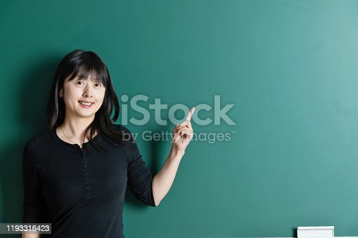 485083346 istock photo Woman pointing at a blackboard 1193316423