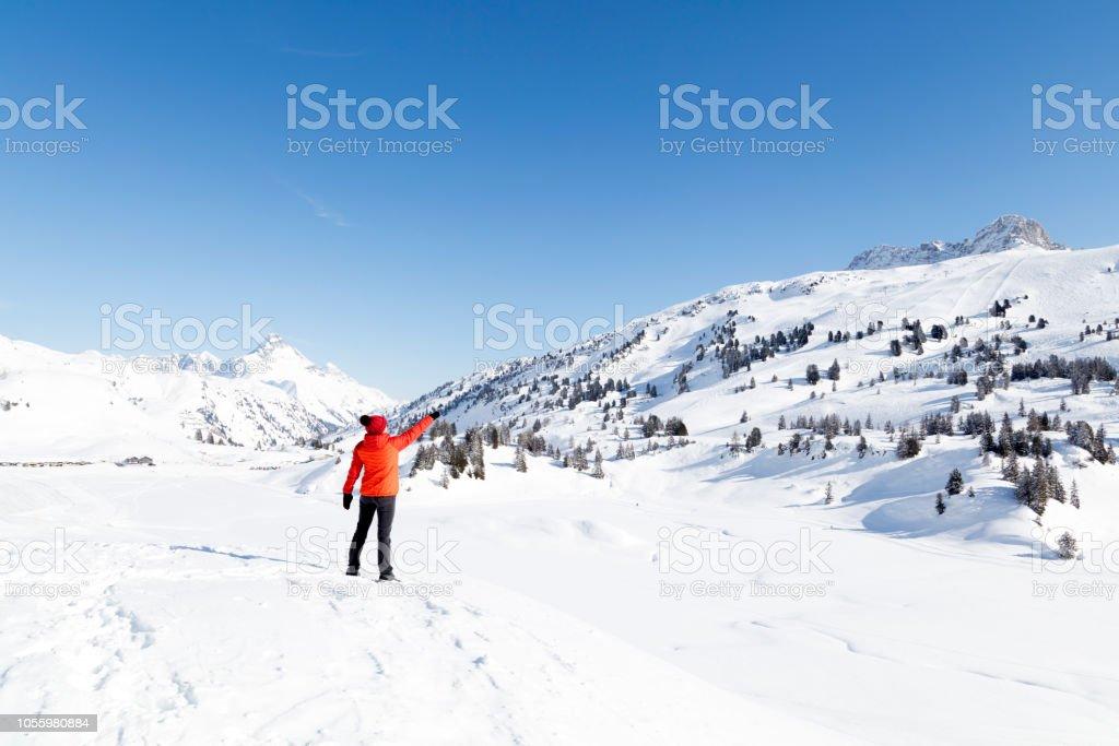 Frau zeigt auf den Gipfel des Berges im Winter – Foto