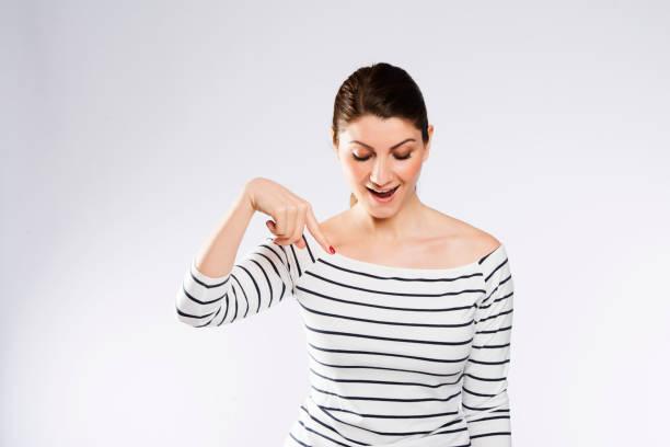 Una mujer apuntando hacia abajo cuando ella está mirando hacia abajo - foto de stock