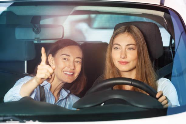 dedo acusador de la mujer en algo sentado en el coche - aprender a conducir fotografías e imágenes de stock