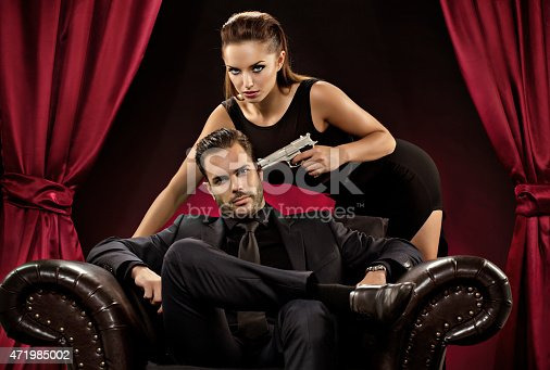 471947536 istock photo woman pointing gun to man sitting on chair 471985002