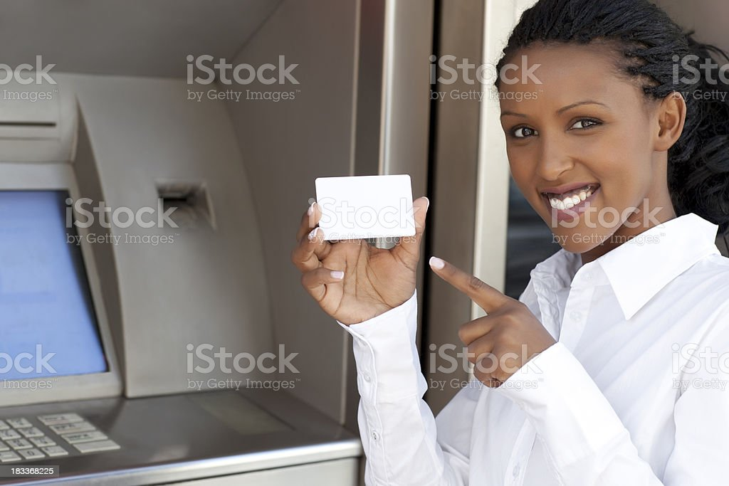 Woman pointing on credit card against the ATM. stock photo