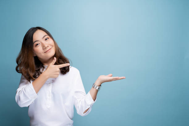 Woman pointing to copy space isolated over blue background stock photo