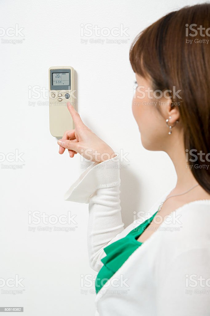 Woman pointing to thermostat 免版稅 stock photo