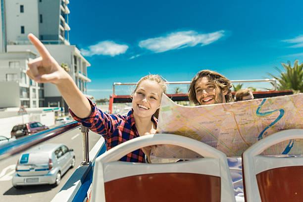 woman pointing while man holding map in tour bus - tour bus stock-fotos und bilder
