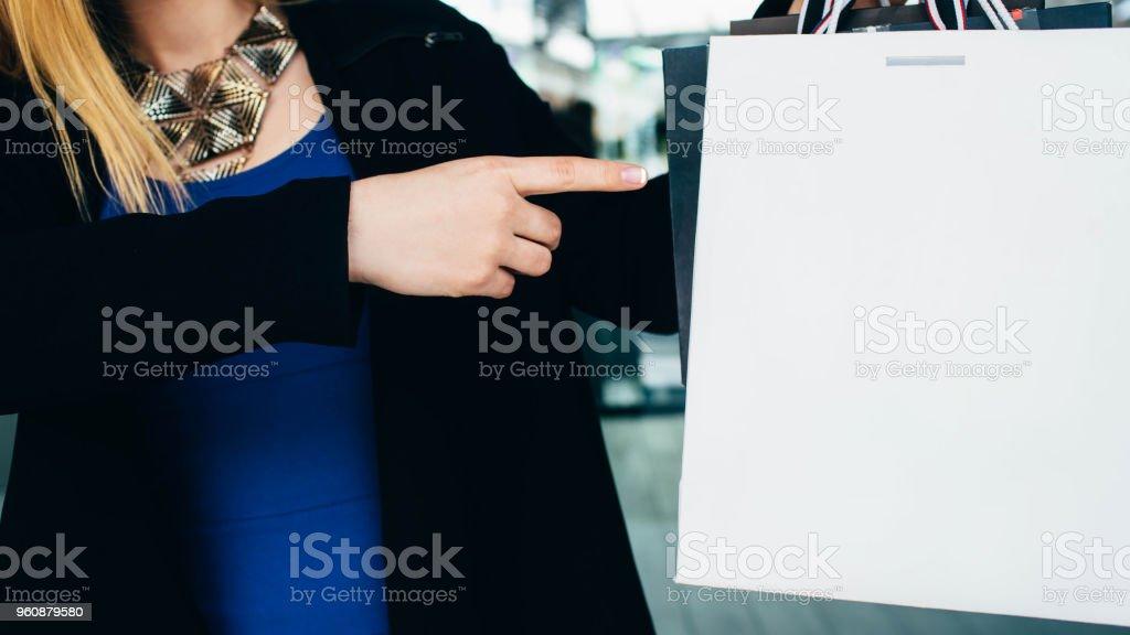 Frau Punkte mit dem Finger auf die Einkaufstasche - Lizenzfrei Ausverkauf Stock-Foto