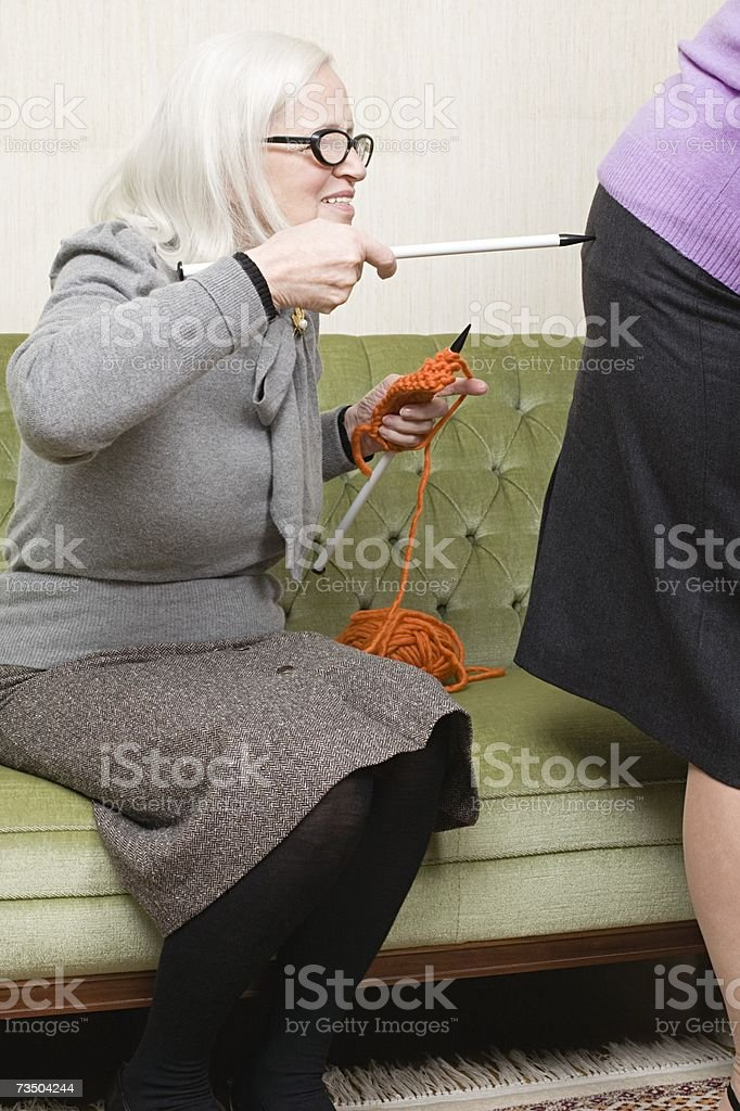Woman poking friend with a knitting needle royalty-free stock photo
