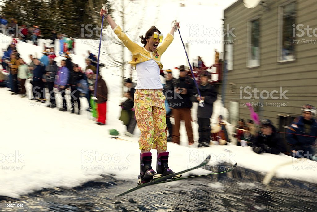 Woman pond skimming at a winter carnival stock photo