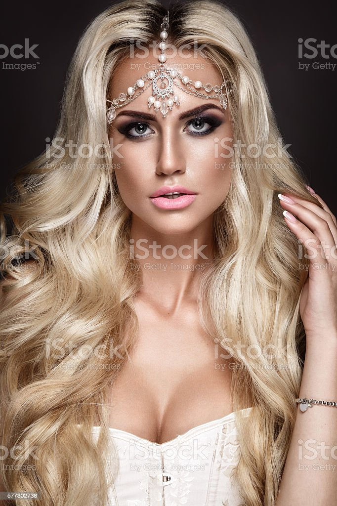 Woman portrait. Blonde young girl posing with jewelry on head. stock photo