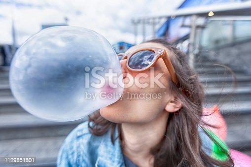 Woman portrait blowing a bubble chewing gum