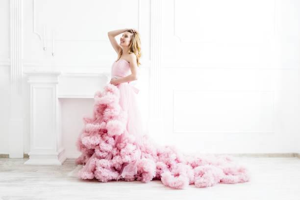 porträt der frau in einem langen rosa kleid auf weiß - tüllkleid stock-fotos und bilder