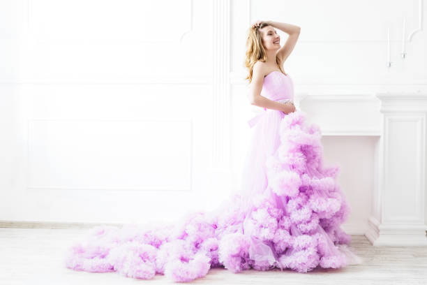 woman portrait in a long pink dress on white - prom fashion stock photos and pictures