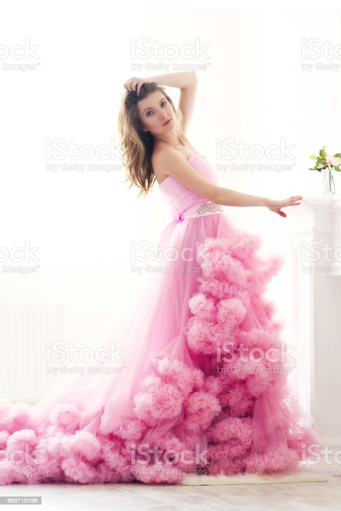 Woman portrait in a long pink dress on white stock photo