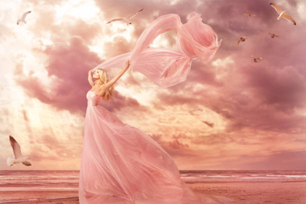 Woman Portrait in Long Dress on Sea Coast, Fantasy Girl Pink Gown with Flying Shawl in Storm Wind stock photo