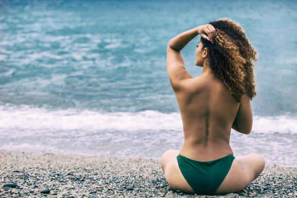 Woman portrait with gorgeous curly hair sitting on beach and looking at sea - fotografia de stock