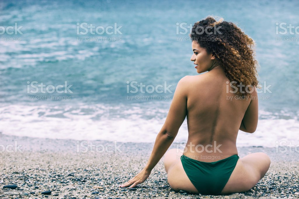 Woman portrait with gorgeous curly hair sitting on beach and looking aside - fotografia de stock