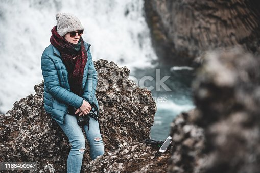 A woman sits on a cliff and poses for a picture against the backdrop of the Hjalparfoss waterfall on the Fossa River.