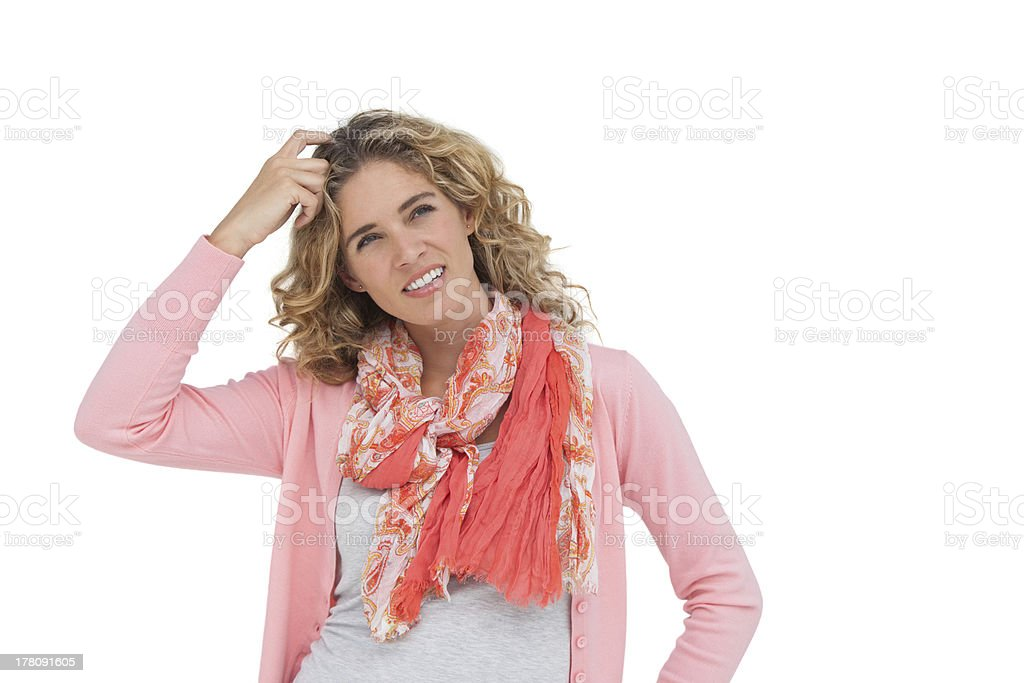 Woman posing and smiling while scratching her head stock photo