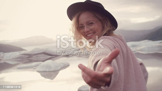 Young woman near beautiful glacier. Looking at camera