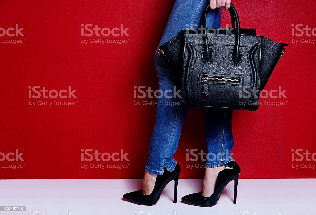 woman posing black high heel shoes and jeans with bag stock photo
