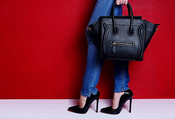 woman posing black high heel shoes and jeans with bag - leder handtaschen damen stock-fotos und bilder