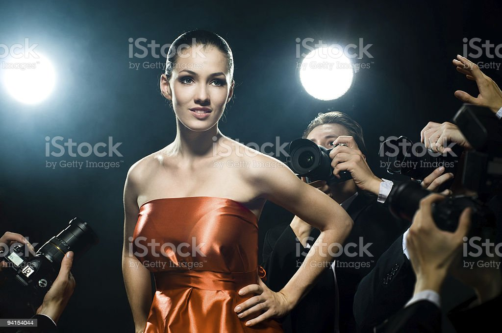 Woman posing for photos taken by the paparazzi royalty-free stock photo