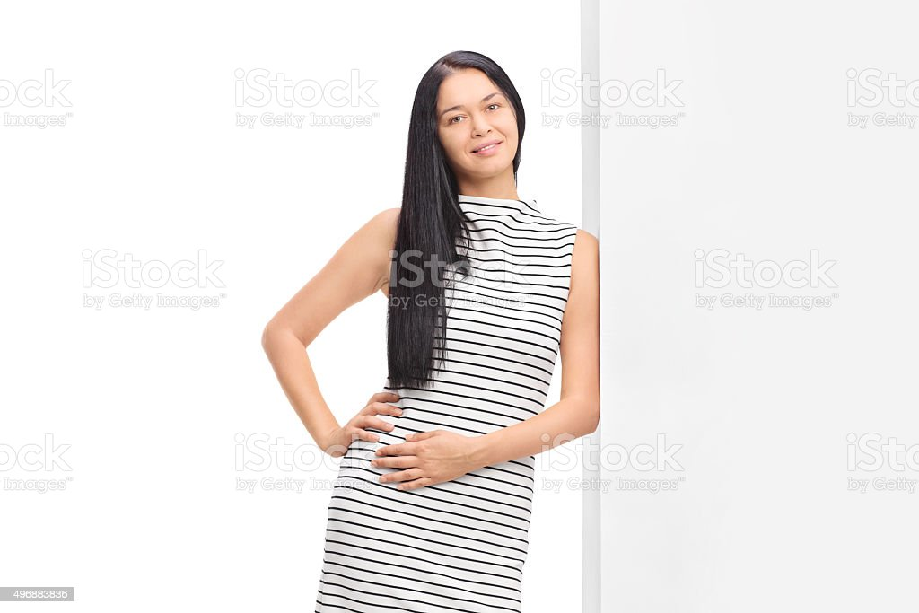 Woman posing in a white dress with black stipes stock photo