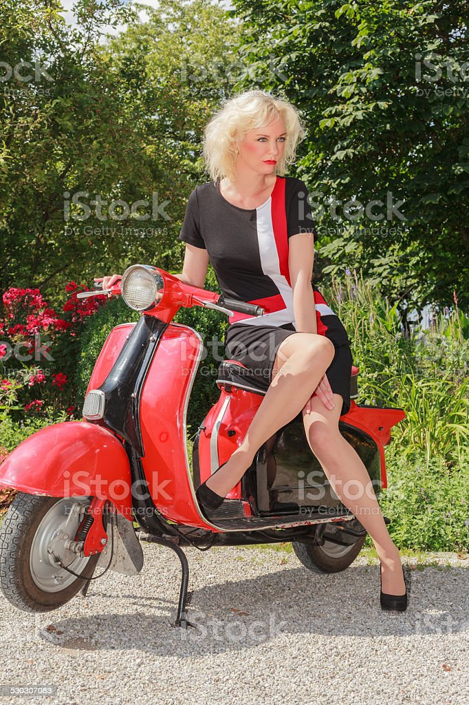 Woman posing in fashionable summer dress on a scooter stock photo