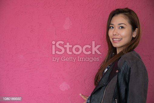 istock A woman posing in front of a pink wall. 1080189332
