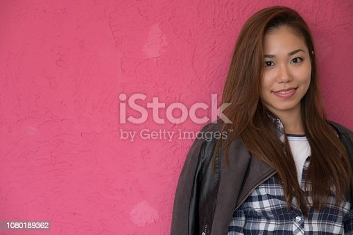 867955978 istock photo A woman posing in front of a pink wall. 1080189362