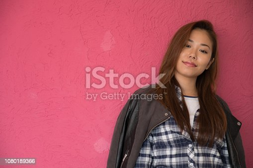 istock A woman posing in front of a pink wall. 1080189366